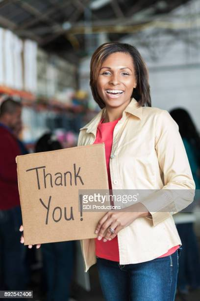 happy woman holds 'thank you! sign during charity event - thank you phrase stock pictures, royalty-free photos & images