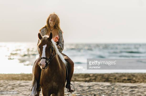 Happy woman horseback riding during summer day on the beach.