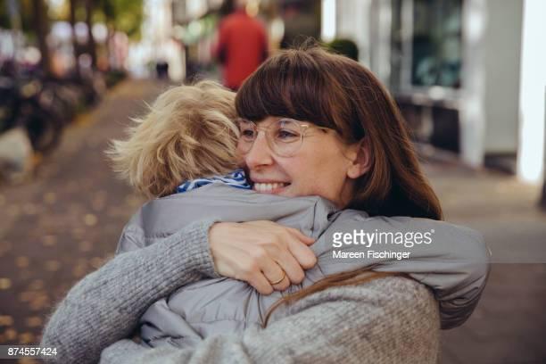 Happy woman hugging boy outside