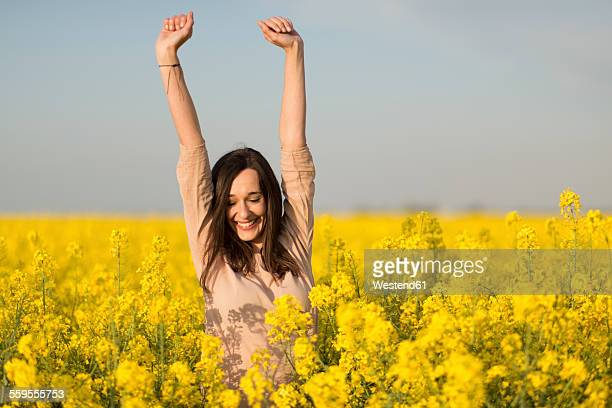 Happy woman in a blossoming rape field