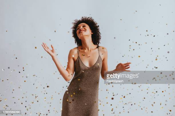 happy woman in a gold dress dancing under confetti - celebratory event stock pictures, royalty-free photos & images