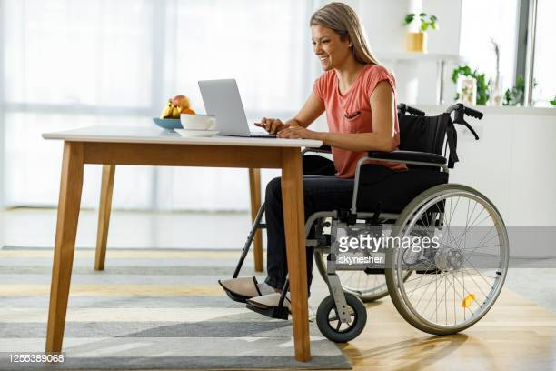 happy woman in a wheelchair working on laptop at home. - disfunção física imagens e fotografias de stock