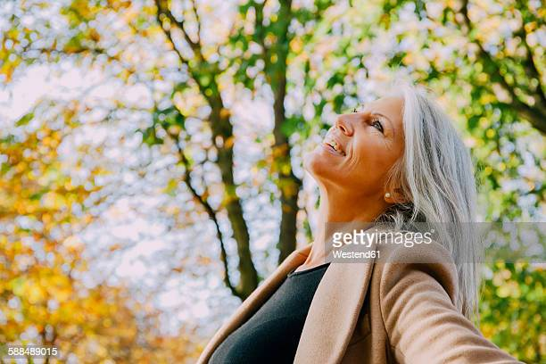 Happy woman in autumnal park looking up