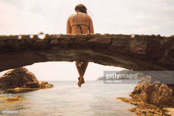 Happy woman in bikini sitting and contemplating the Costa brava water with nice sunset light in summer during travel vacations in the Catalonia region.