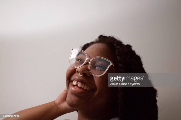 happy woman in eyeglasses looking away against wall - cat's eye glasses stock pictures, royalty-free photos & images