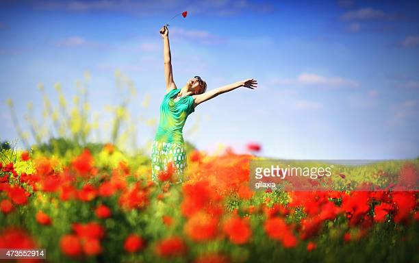 Happy woman in flower garden with arms raised.
