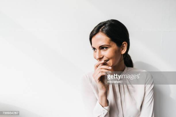 Happy woman in front of white wall