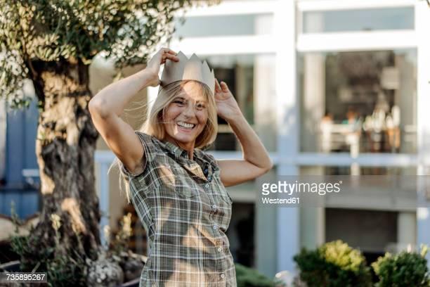 Happy woman in garden wearing a crown