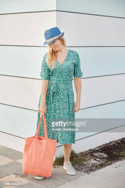 happy woman in green dress and hat smiling in front of striped wall - トートバッグ ストックフォトと画像