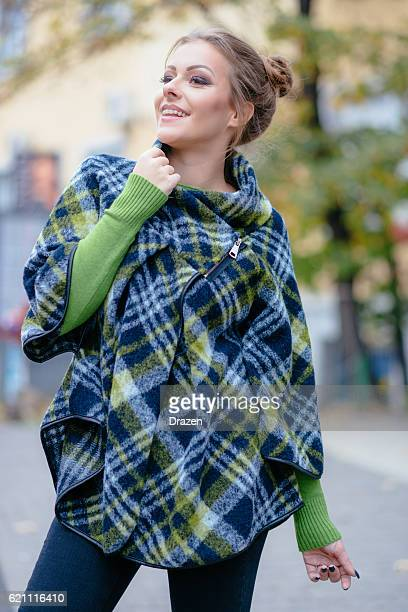 happy woman in green plaid poncho and smart casual clothing - poncho stock pictures, royalty-free photos & images