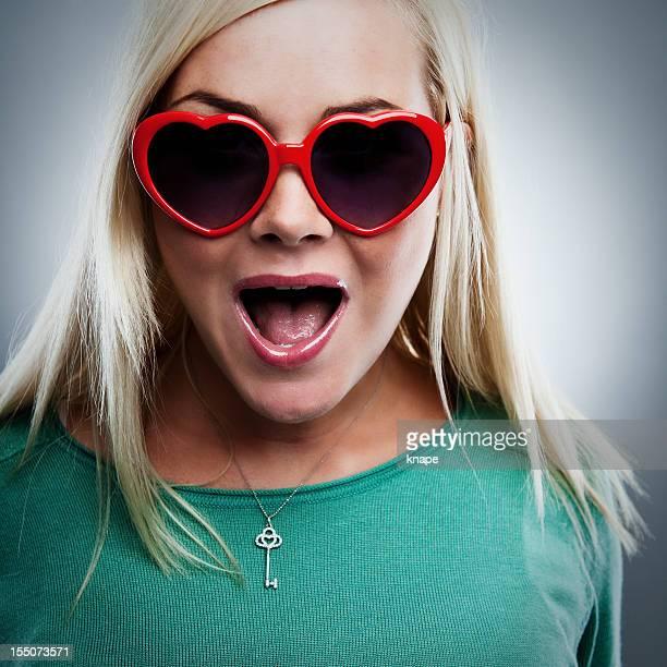 Glückliche Frau mit herzförmigen Brille