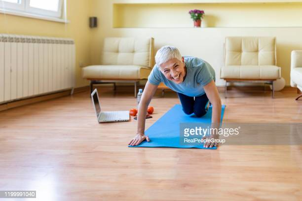 happy woman in her 50s stretching for exercise at home. joy of life and freedom in movement, concept. - core stock pictures, royalty-free photos & images