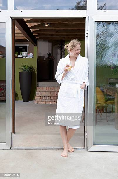 A happy woman in her bathrobe leaning in the doorway of her house