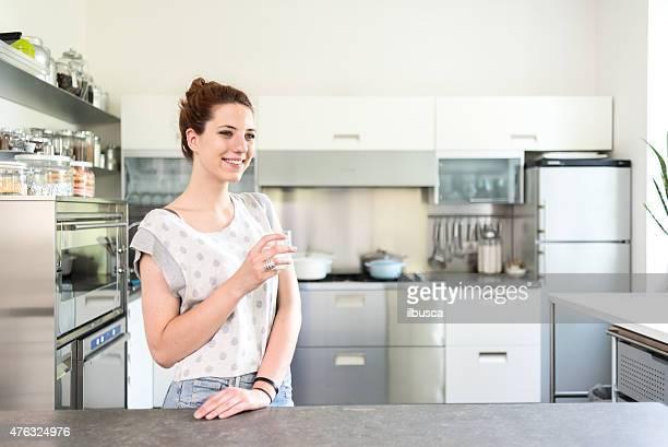 幸せな女性の彼女の新しいキッチン