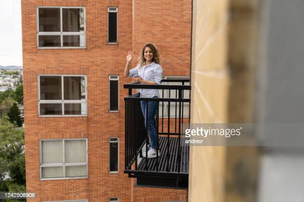 happy woman in lockdown greeting her neighbor from the balcony - balcony stock pictures, royalty-free photos & images