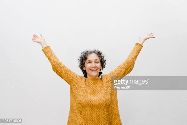 happy woman in orange sweater standing with arms raised against white wall - オレンジ色のシャツ ストックフォトと画像