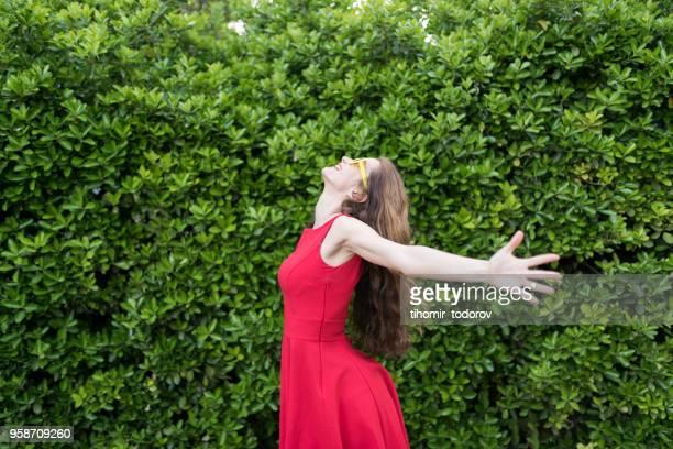 両腕に赤いドレスで幸せな女 - 赤のドレス ストックフォトと画像