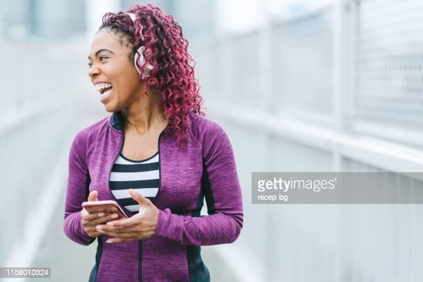 mulher feliz na roupa dos esportes usando o telefone esperto - só uma mulher de idade mediana - fotografias e filmes do acervo