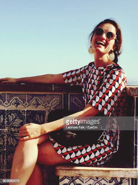 Happy Woman In Sunglasses Sitting On Chair Against Sky