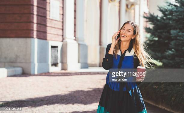 happy woman in the city talking on phone - one young woman only stock pictures, royalty-free photos & images