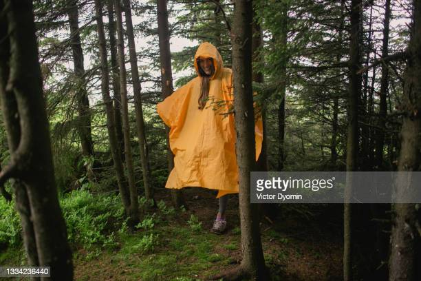 happy woman in the orange raincoat in the forest - national wildlife reserve stock pictures, royalty-free photos & images