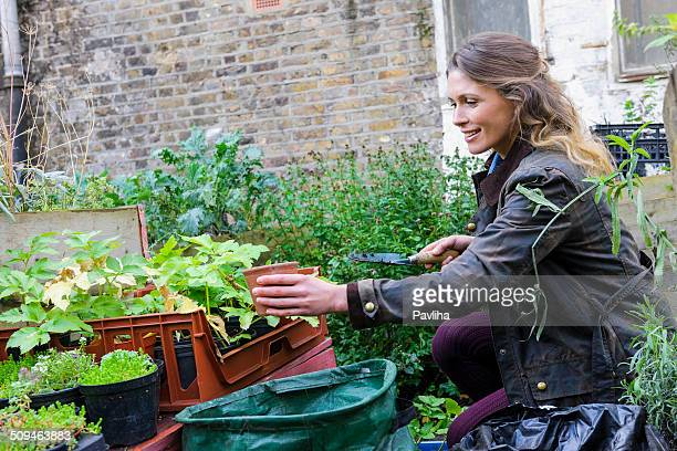 Happy Woman In Urban City Garden Potting Plants, London, UK