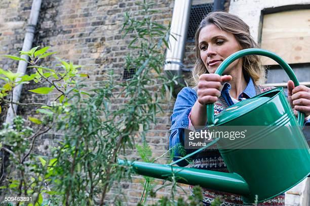 Happy Woman In Urban City Garden Watering Plants, London, UK