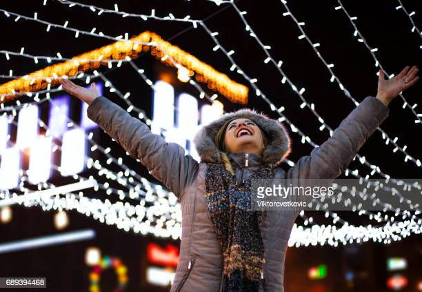 Happy woman in winter decorated city street
