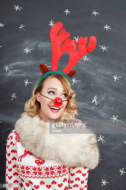 Happy woman in winter outfit and reindeer antlers headband
