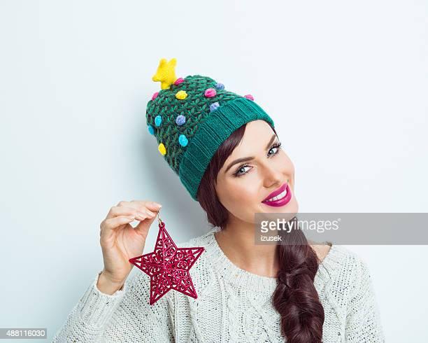 Glückliche Frau im winter outfit holding Rot kleinen star