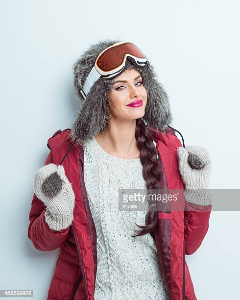 Happy woman in winter outfit, wearing fur cap and goggle