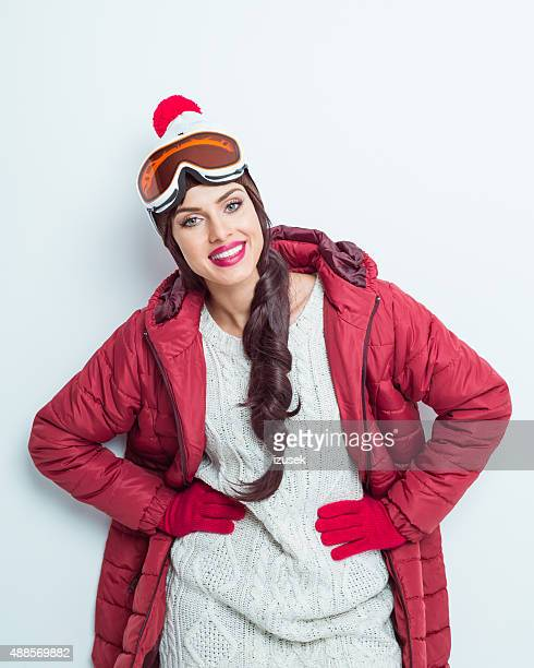 Happy woman in winter outfit, wearing woolen cap and goggle
