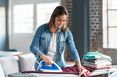 Happy woman ironing her clothes at home
