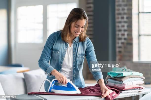 Glückliche Frau Bügeln ihrer Kleidung zu Hause