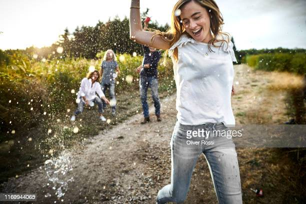 happy woman is being splashed on dirt road in the countryside - outdoors stock-fotos und bilder