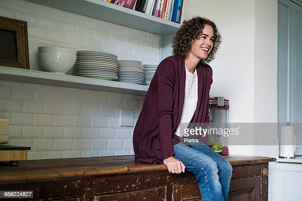 Happy woman is sitting on kitchen counter