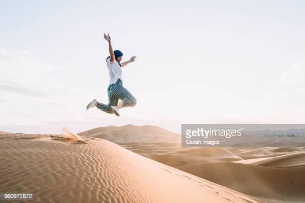 happy woman jumping at merzouga desert against sky - camel active stock-fotos und bilder