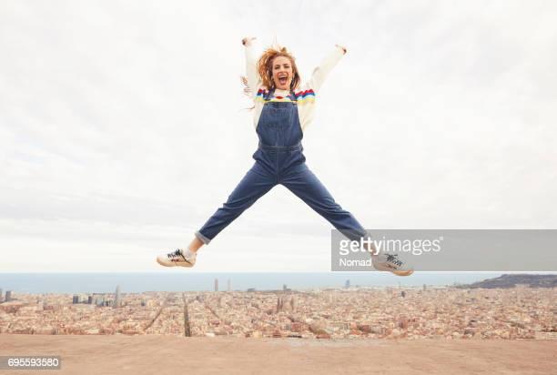 Glückliche Frau springen in der Luft gegen Stadtbild