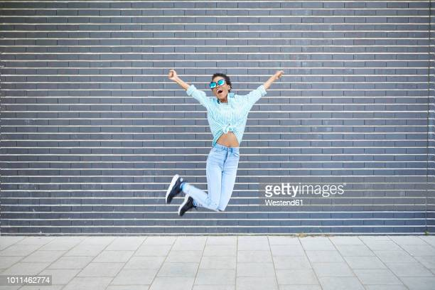 happy woman jumping in the air in front of grey facade - erfolg stock-fotos und bilder