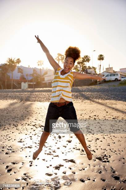 Happy woman jumping in the air on the beach