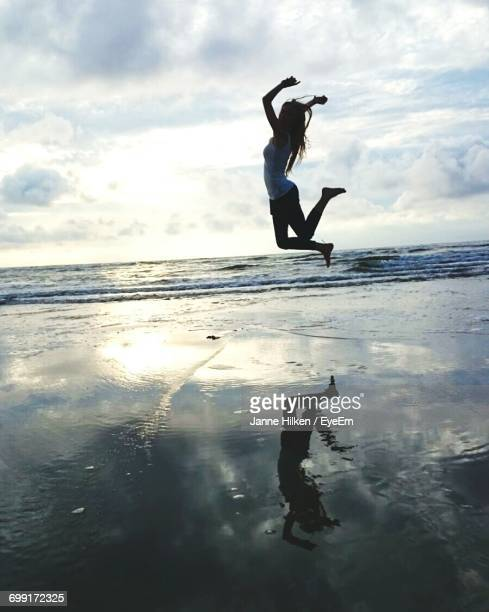 Happy Woman Jumping On Beach Against Sky