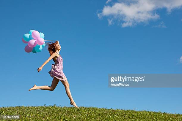Happy woman jumping on meadow with balloons