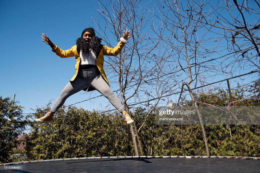 Happy woman jumping on trampoline outdoors in springtime. : Stock Photo