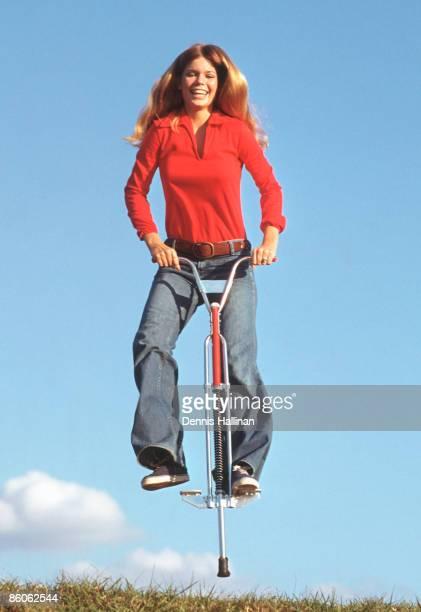 Happy woman jumping using pogo stick