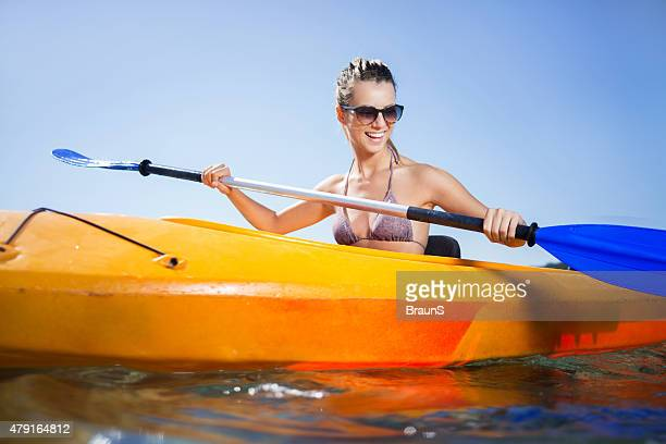 Happy woman kayaking at sea during summer day.