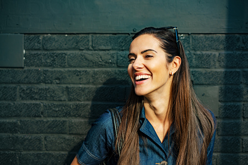 Happy woman laughing off camera - gettyimageskorea