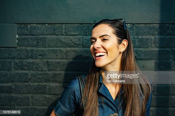 happy woman laughing off camera - brown hair stock pictures, royalty-free photos & images