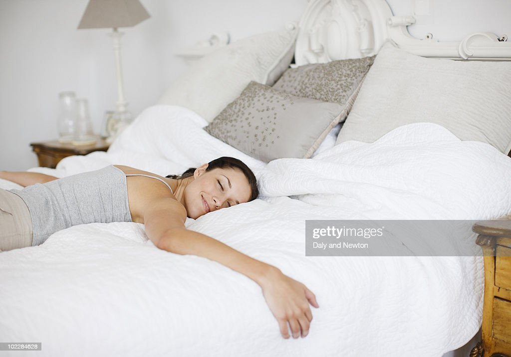 Happy woman laying on bed : Stock Photo