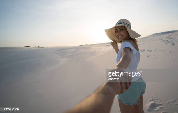 happy woman leading the way while traveling in the desert - maranhao state stock pictures, royalty-free photos & images