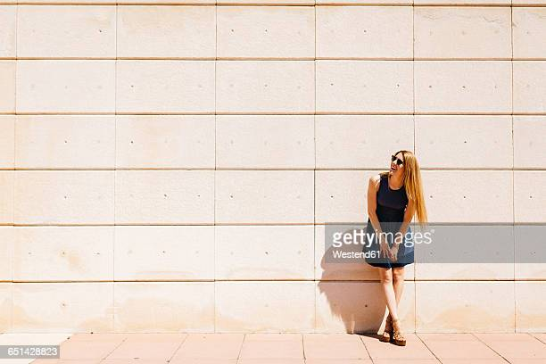 Happy woman leaning against wall in summer